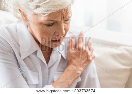 Malaise. Aged lady is sitting on couch and feeling joint pain. She is touching her shoulder expressing suffering. Copy space in the right side