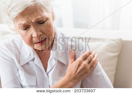 Joint pain. Senior woman is touching her arm while expressing suffering. Copy space in the right side