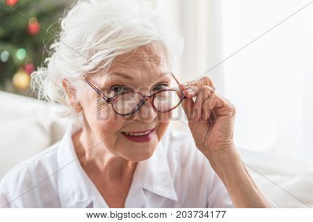 Positive mood. Close-up portrait of elegant elderly lady who is expressing gladness. She is looking at camera with joy while touching her glasses