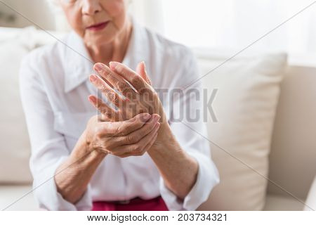 Arthritis. Close-up of hands of unhappy senior lady is feeling arm ache and expressing suffering. Copy space in the right side
