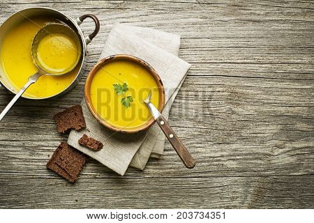 Healthy vegetable cream soup with bread on wooden background