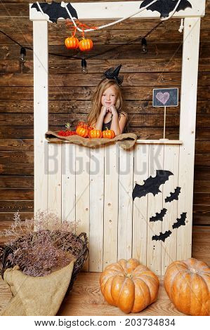 Little Girl Dressed As A Witch Sells Pumpkins