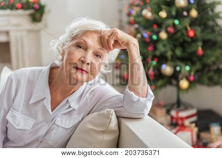 Feeling tired. Sad elderly woman is looking at camera thoughtfully while leaning on elbow and touching her face. She is sitting on sofa with Christmas tree and gift boxes on background