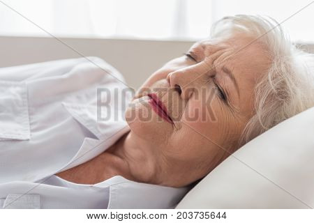 Bad dream. Close-up of face of sleeping elderly woman who is lying on couch. She is frowning with closed eyes