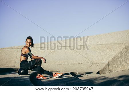 Healthy lifestyle. Young woman sitting and resting on a fitness ball outdoors. Female taking a rest after exercising outdoors.
