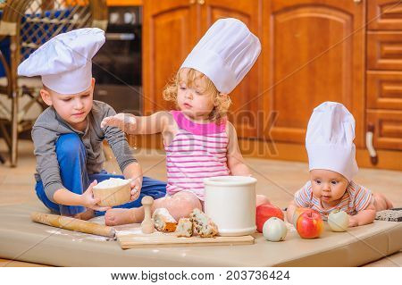 Cute siblings, boy and girl, and a newborn kid with them in chef's hats sitting on the kitchen floor soiled with flour playing with food making mess and having fun
