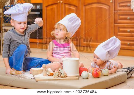 Two siblings and a newborn kid with them in chef's hats sitting on the kitchen floor soiled with flour playing with food making mess and having fun