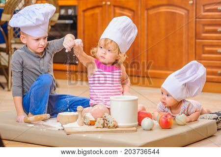 Cute boy and girl and a newborn kid with them in chef's hats sitting on the kitchen floor soiled with flour playing with food making mess and having fun