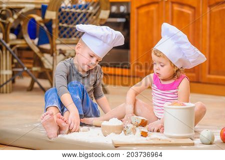 Making mess: two siblings - boy and girl - in chef's hats sitting on the kitchen floor soiled with flour playing with food and having fun