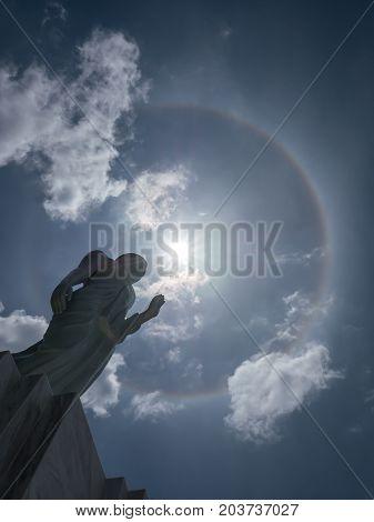 Buddha statue and sun halo on blue sky background