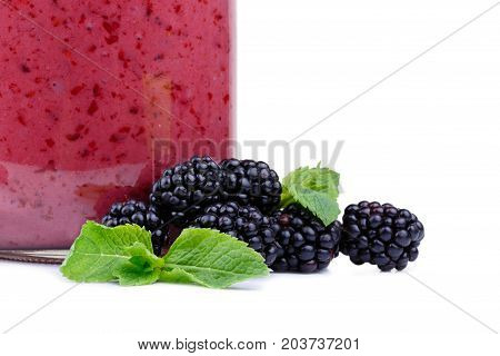 Close-up of a heap of natural blackberries with fresh mint, isolated on a white background. A mason jar full of yogurt near a pile of berries. Juicy, healthful, organic and refreshing concept.