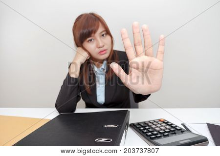Business woman says no or hold on at her office.