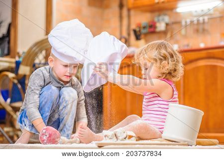 Cute children in chef's hats sitting on the floor soiled with flour, playing with food
