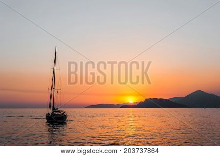 Tranquil nature scene of sailing boat in the ocean at sunset