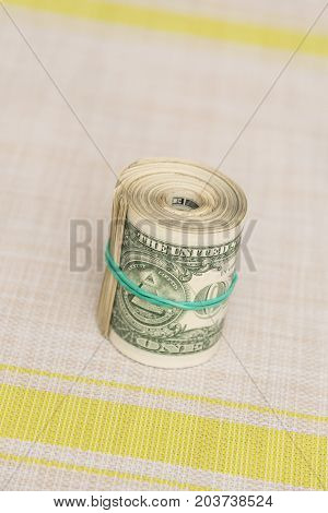 A bundle of money twisted into a bundle and bound by a green rubber band on a light textured background