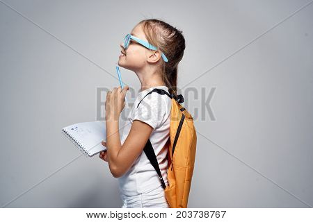 little girl with glasses and with a backpack holding a pen.
