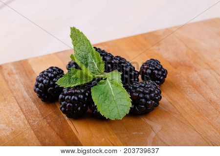 A close-up picture of a heap of blackberries on a brown wooden background. A pile of juicy berries full of nutritious and healthy vitamins with mint on a cutting desk. Summer vegetarian ingredients.