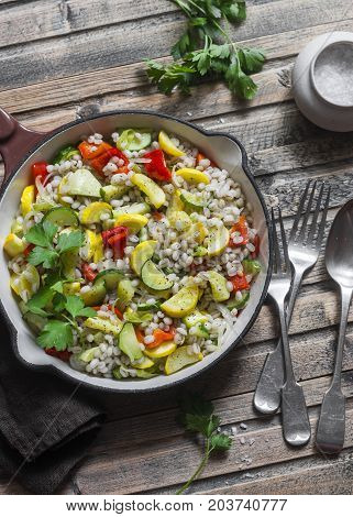 Pearl barley with seasonal garden vegetables in pan on wooden background top view. Zucchini sweet pepper squash and barley stew. Vegetarian food concept
