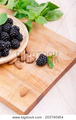 A close-up of a partial composition of a plate with a pile of sweet, organic, ripe blackberries on a light brown wooden background. Almonds and fragrant mint on a cutting desk. Copy space.
