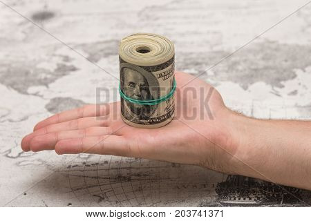 A man holds a bunch of money, twisted in a bunch and tied with a green rubber band on a light textured background
