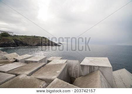 Plenty of heavy cubes lying in pile on shore of Asturias, Spain forming breakwater.