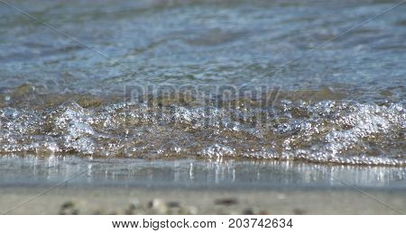 Water rolling up to sandy beach edge at eye level
