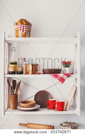 White wooden shelf - kitchen furniture in rustic style with utensils and bright decorative details
