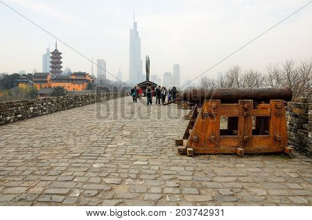 January 2 2015. Nanjing China. Chinese tourists near old weathered cannons on the Nanjing city wall on an overcast day in Jiangsu province China with Jiming temple and Zifeng Tower in the background.