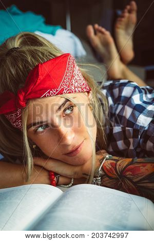 Portrait of a young blonde closeup. Distracted from reading and looking wistfully out the window. Wears a red headband and plaid shirt. Modern student.