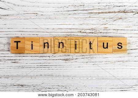 TINNITUS word made with wooden blocks concept