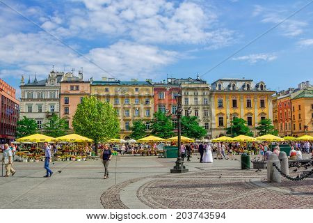 Krakow/Poland- August 15, 2017: view of main Market Square with walking tourists, souvenirs and flowers sellers and colorful old houses on background, sunny summer day, blue sky