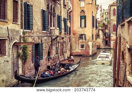 Venice, Italy - May 20, 2017: The gondola with tourists floats along the old narrow canal. Gondola is the most attractive tourist transport in Venice.
