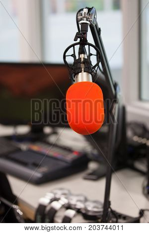 An orange microphone in a podcast or radio studio with headphones, monitor and mixer in the background