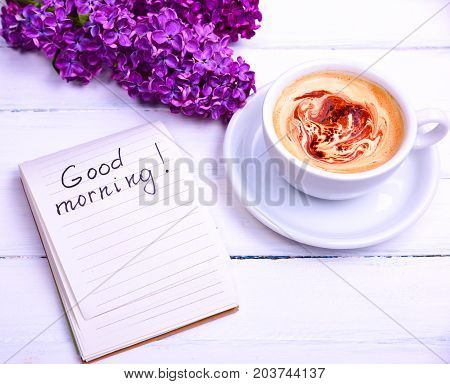 Cappuccino in a white cup and saucer and a paper notepad with the inscription of good morning on a white wooden background top view