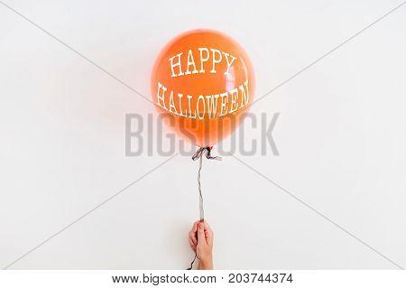 Halloween minimal concept. One orange balloon on white background. Flat lay top view.