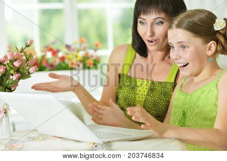Smiling mother and daughter sitting at table and looking at laptop