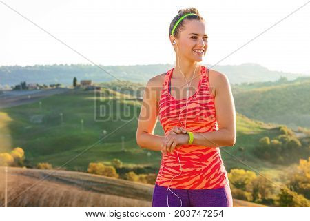 Fit Woman Looking Into The Distance And Using Activity Tracker
