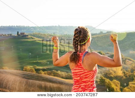 Fit Woman Jogger In Front Of Scenery Of Tuscany Rejoicing