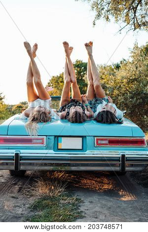 Three girls are lying on the trunk and raised their legs up