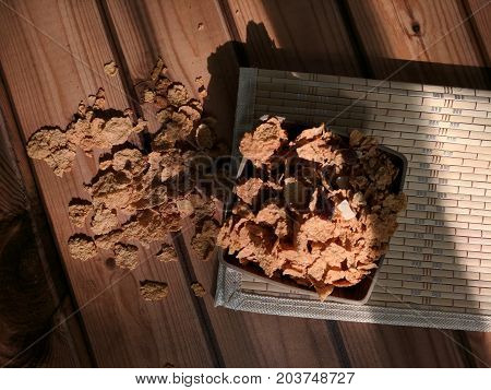 corn flakes placed on wooden mat in low light