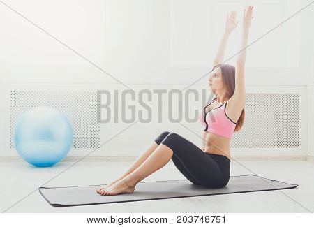 Fitness woman lying doing crunches barefoot at gym. Young sporty girl doing sits-up on mat. Healthy lifestyle, gymnastics, weightloss concept