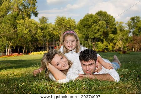 daughter, mother and father playing outside on a sunny day