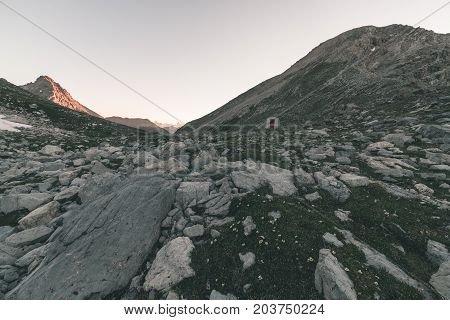Alpine Meadow And Pasture Set Amid High Altitude Mountain Range At Sunsets. The Italian Alps, Famous