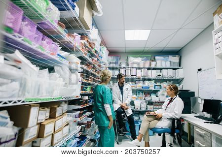 Medical staff discussing in hospital pharmacy. Doctors and nurse talking in hospital pharmacy.