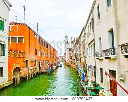 The blurred image of the venetian canals with boats across the canal at rainy day.