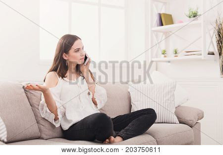 Serious girl talking on mobile phone displeased with conversation, question on her face, copy space