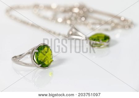 Beauty silver ring and pendant with peridot on white acrylic desk.