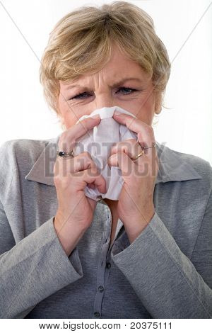 senior woman in 50s sneezing, flu or allergy