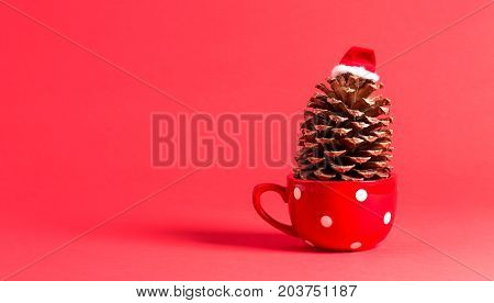 Christmas themed pinecone with santa hat on red