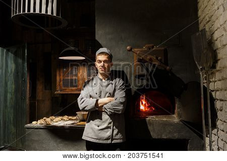 Young male baker cook standing at stove. Confident man in cook uniform standing at kitchen, raw dough and burning stove on background, copy space